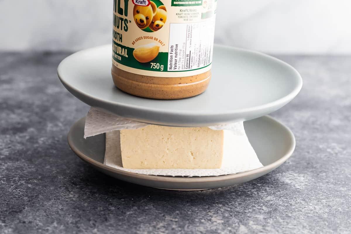 tofu kağıt havlular, tabaklar ve üstüne bir kavanoz fıstık ezmesi ile bastırılır