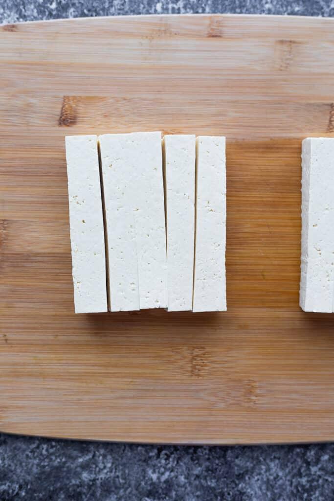 block of tofu cut into stick on cutting board