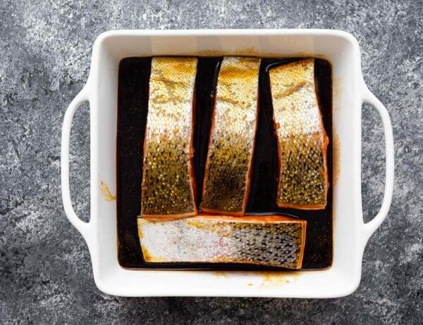 salmon skin side up in marinade in white baking dish