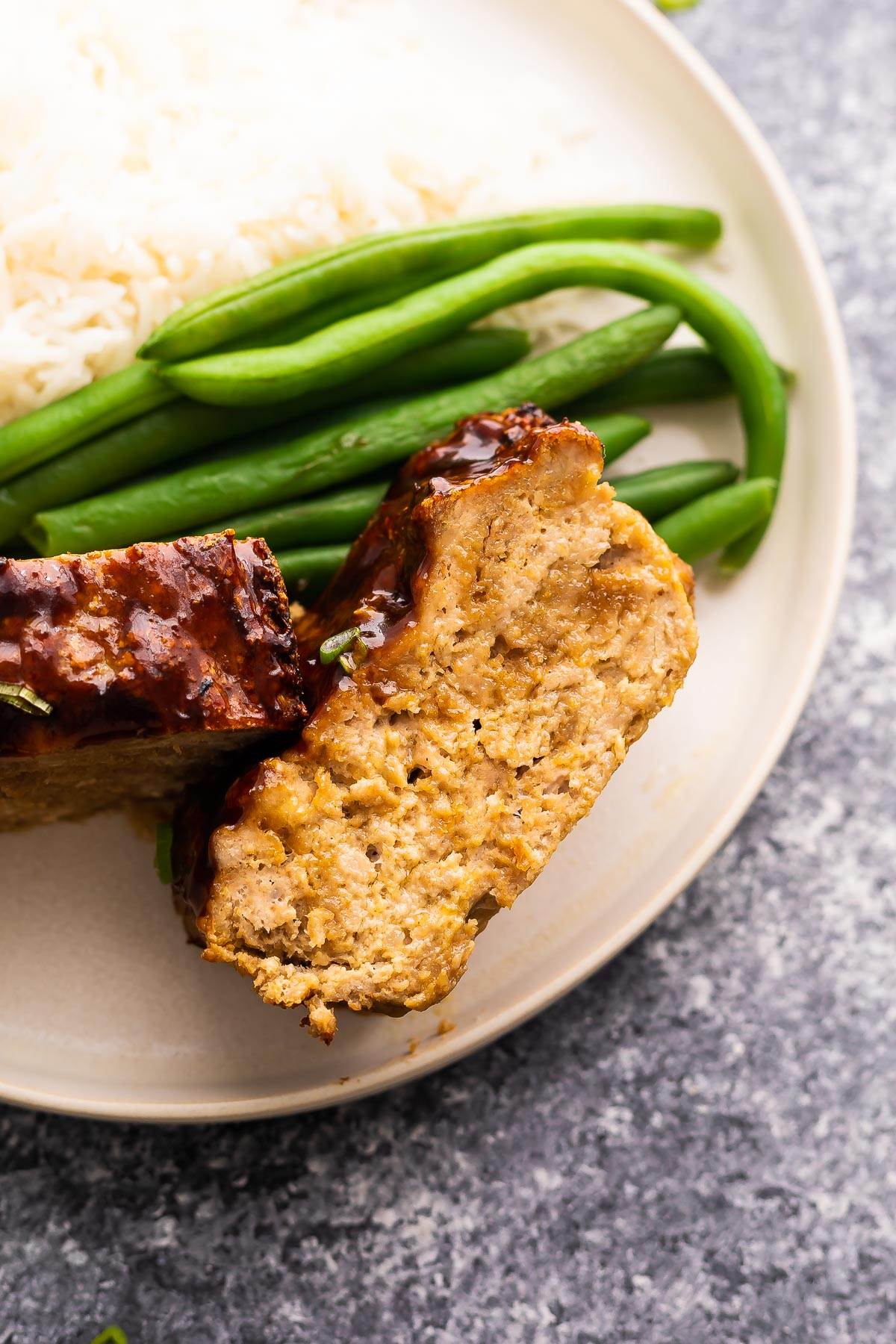 close up shot of turkey meatloaf on a plate with green beans
