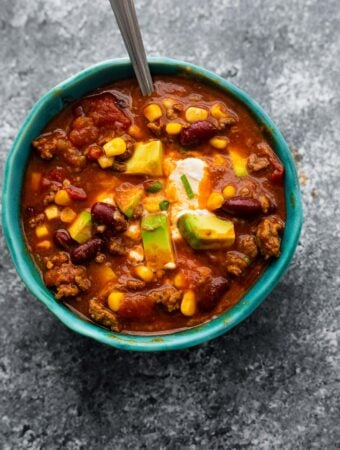 instant pot chili in blue bowl garnished with sour cream, cheese and avocado