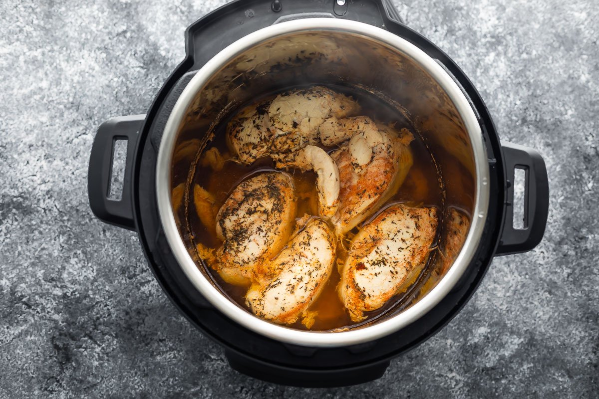 overhead view of cooked chicken breast in the instant pot in liquid
