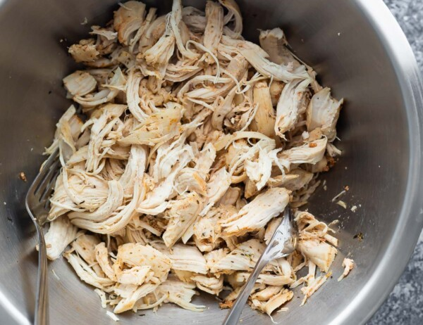 shredded chicken in a bowl with two forks