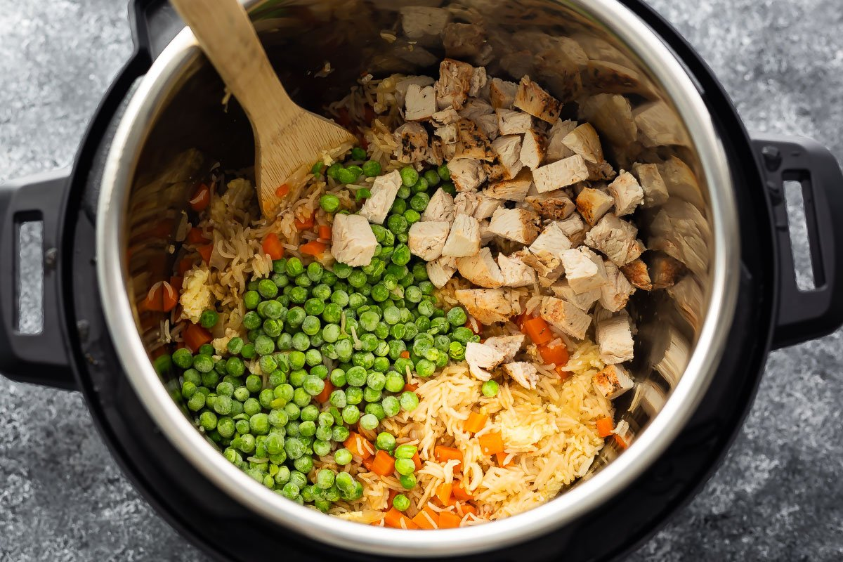 overhead view of fried rice topped with peas and chicken in instant pot