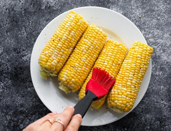brushing olive oil onto corn on the cob using a silicone brush