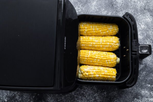 overhead view of four ears of corn in the air fryer basket (before cooking)