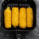 overhead view of four ears of corn in the air fryer basket (after cooking)
