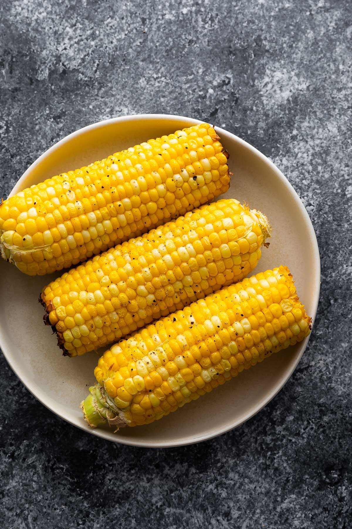 3 ears of cooked corn on white plate