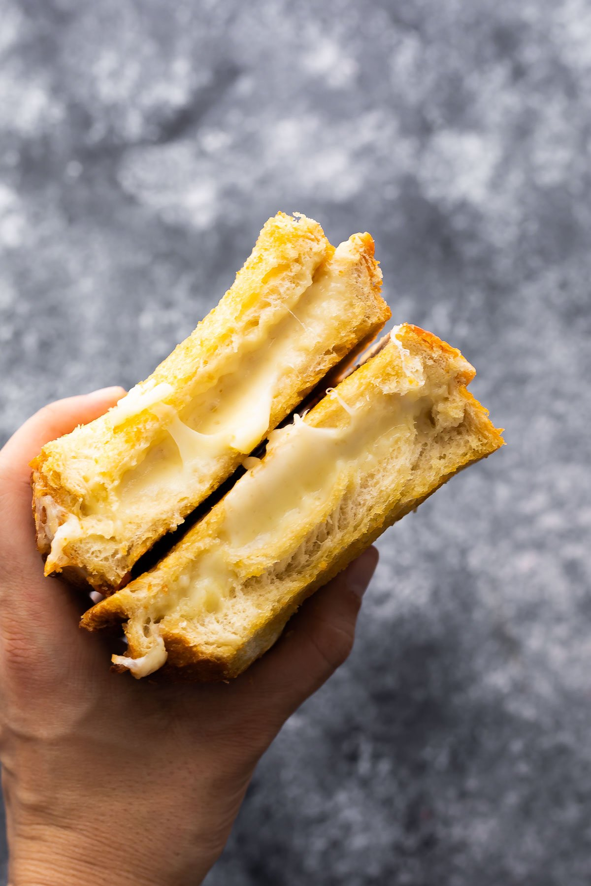 yapışkan peynir ortaya çıkaran iki parça ızgara peynir tutan el