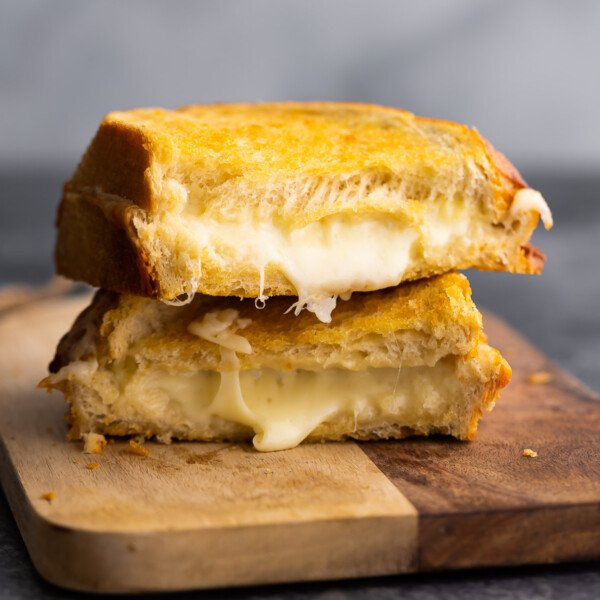 grilled cheese stacked on cutting board revealing melted cheese