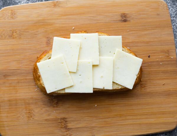 cheese arranged on sourdough bread on cutting board