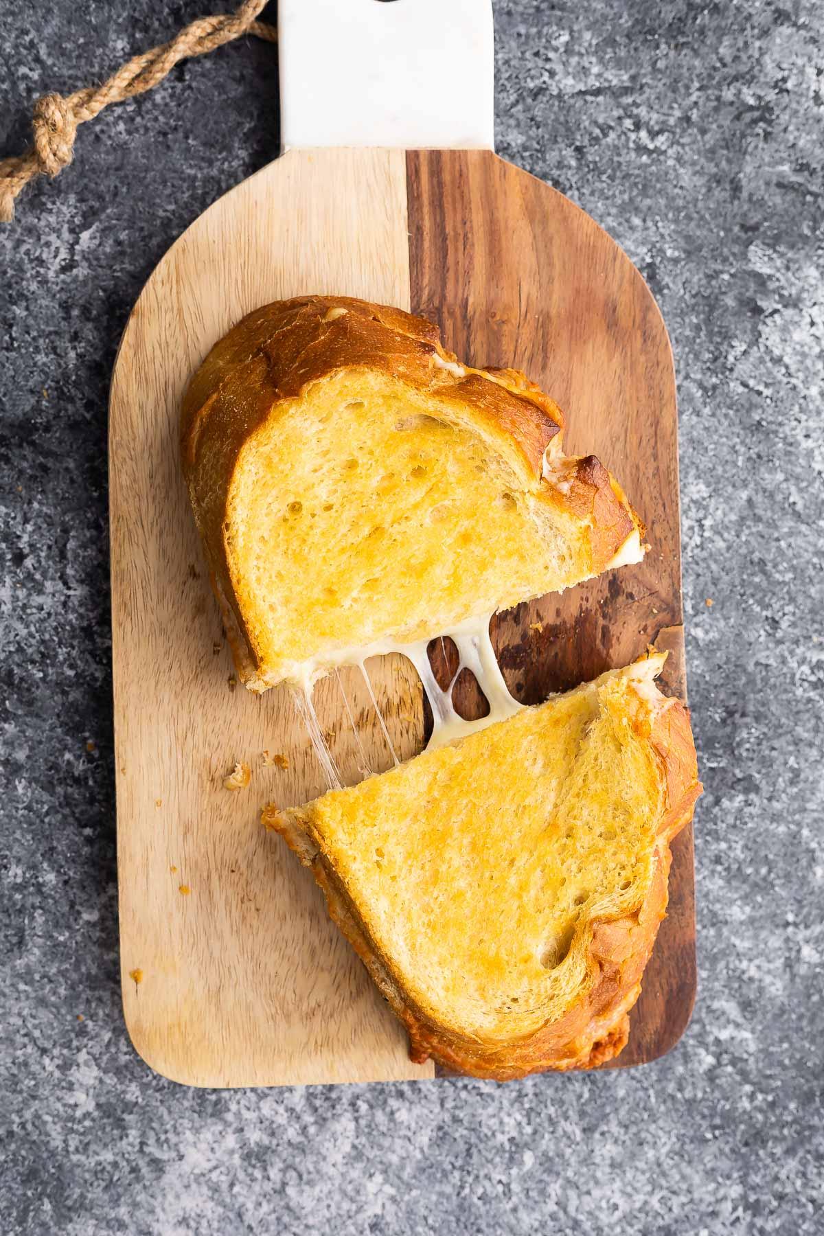 kesme tahtası üzerinde ızgara peynir, yapışkan peyniri açığa çıkaran parçalara ayrılmış