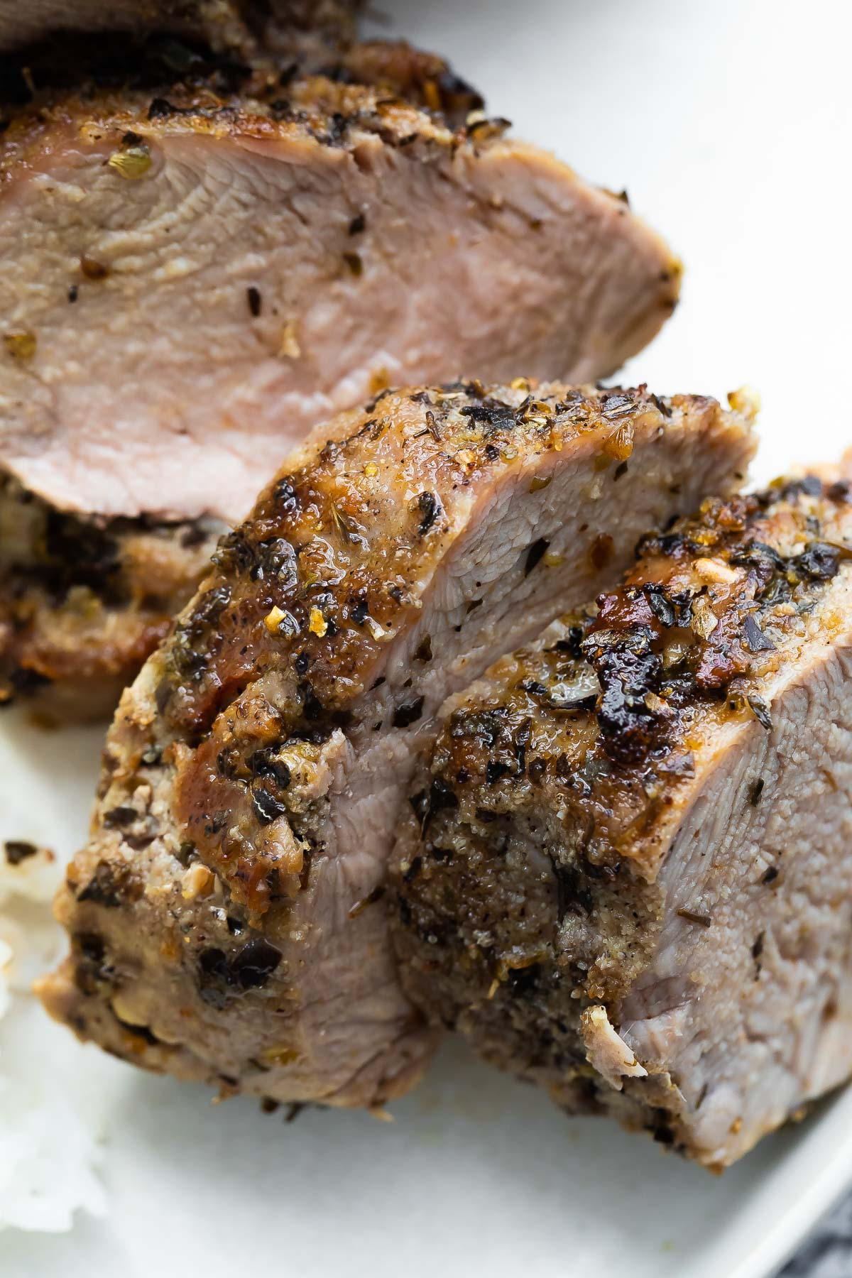 close up shot of sliced pork tenderloin showing the herbs and brown crust on surface