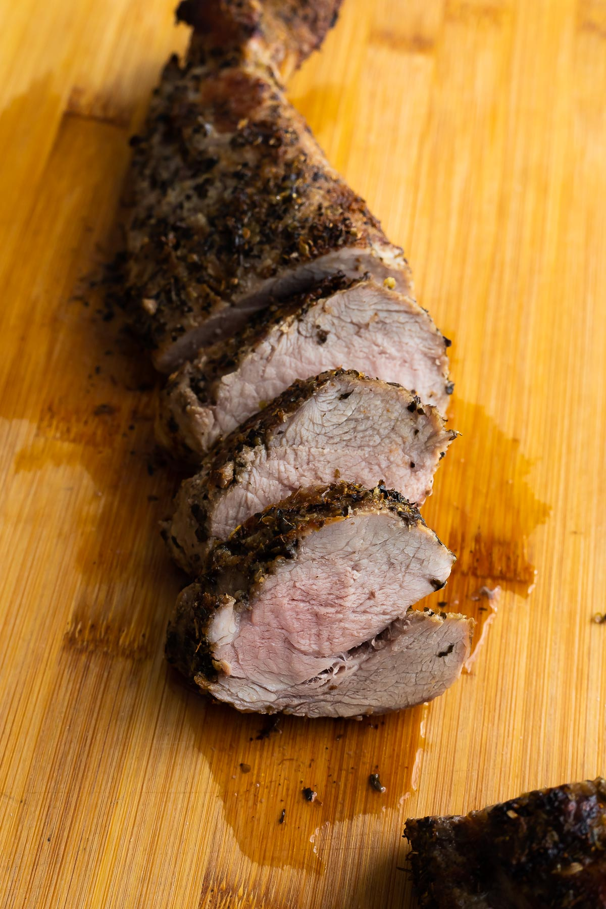 side angle view of sliced pork tenderloin on cutting board
