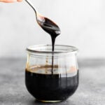 spoon drizzling thick balsamic reduction into a jar