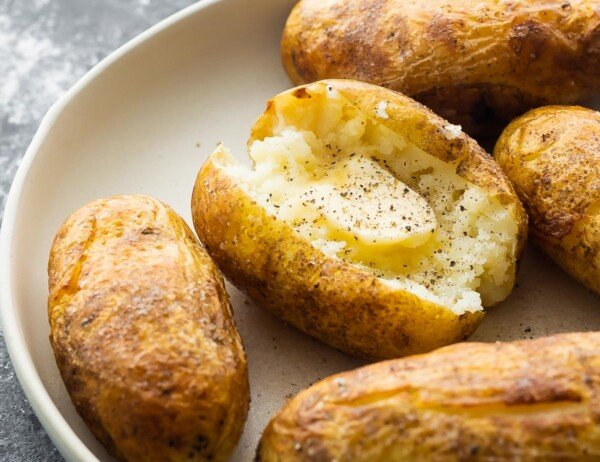 instant pot baked potato broken open with melted butter and pepper