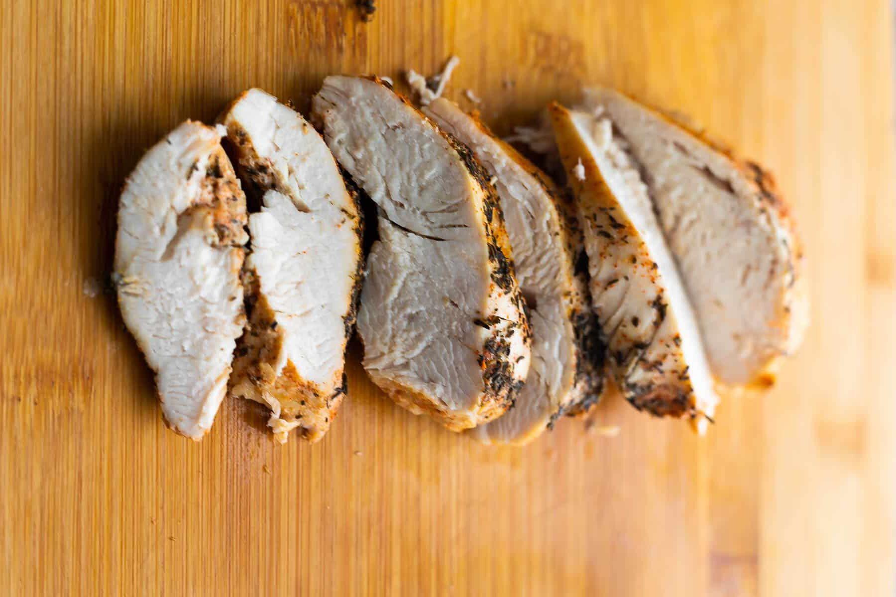 kesme tahtası üzerinde dilimlenmiş tavuk göğsü