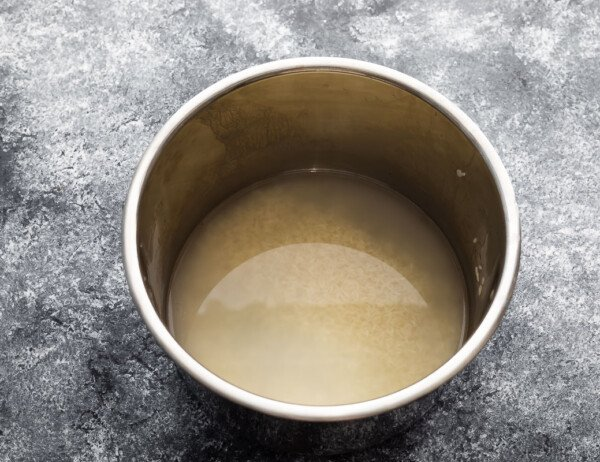 jasmine rice in instant pot insert covered in cloudy water