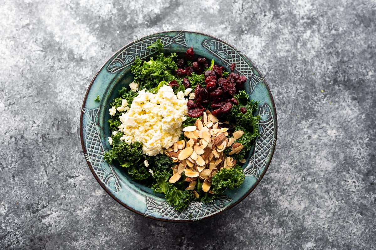 kale in salad bowl with almonds, cranberries and feta cheese