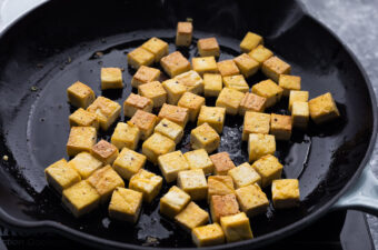 golden, crispy tofu being fried in pan with oil