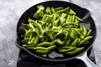 cooking broccoli and snap peas in frying pan