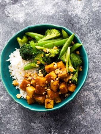 overhead view of peanut tofu in bowl with rice and green vegetables