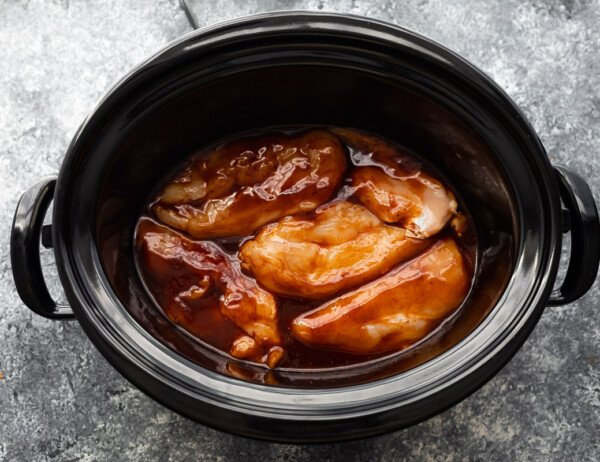 overhead view of bbq chicken in the slow cooker before cooking