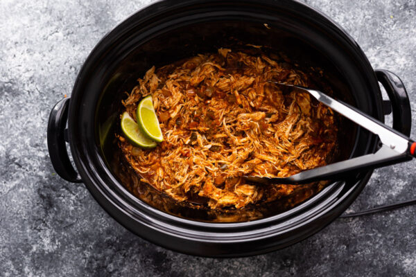 shredded salsa chicken in slow cooker with tongs and two lime wedges