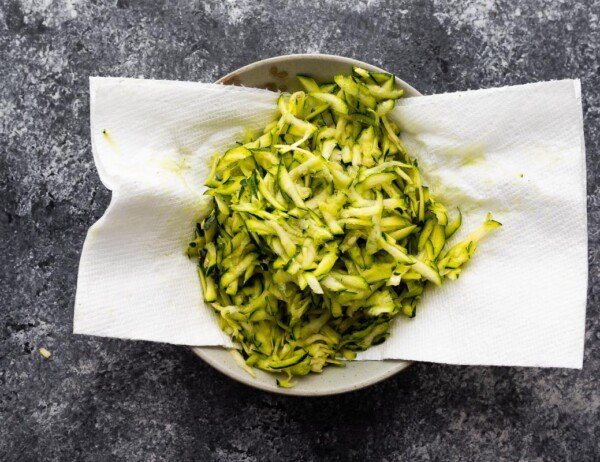 shredded zucchini on a paper towel lined plate