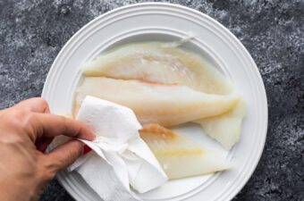 blotting white fish dry with paper towel