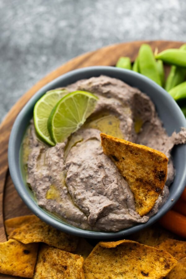 pita chip in bowl of black bean hummus showing creamy texture