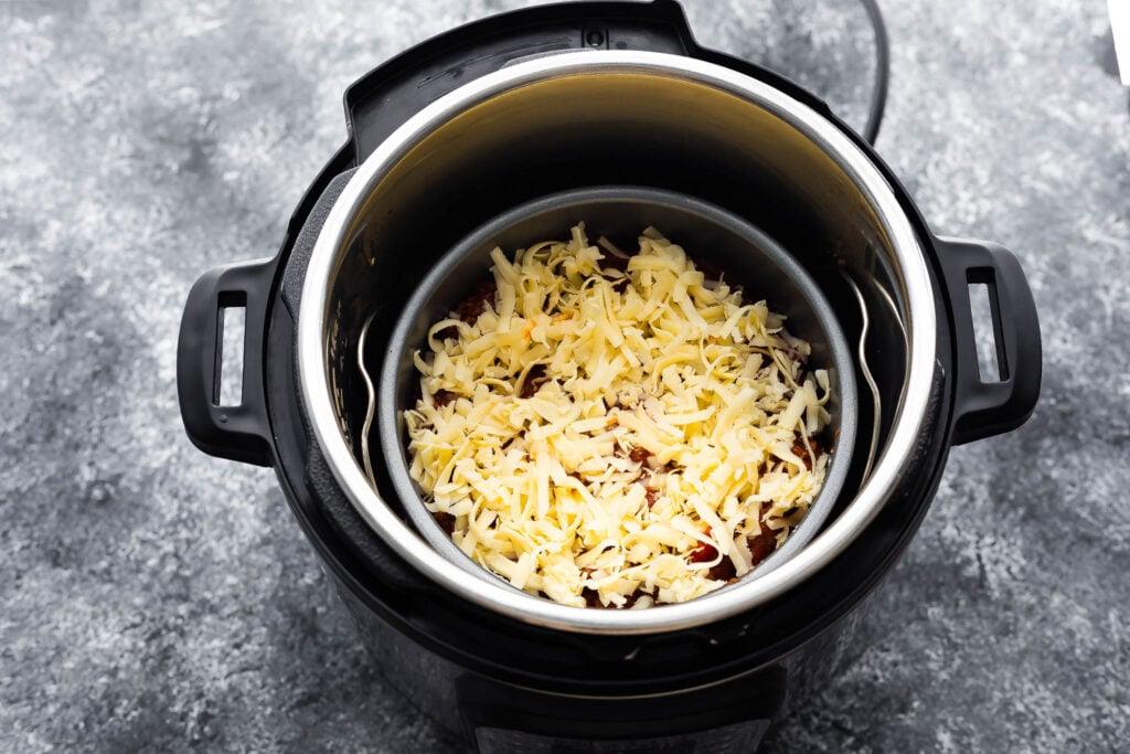 fifth layer of lasagna (mozzarella) in cake pan on trivet in instant pot