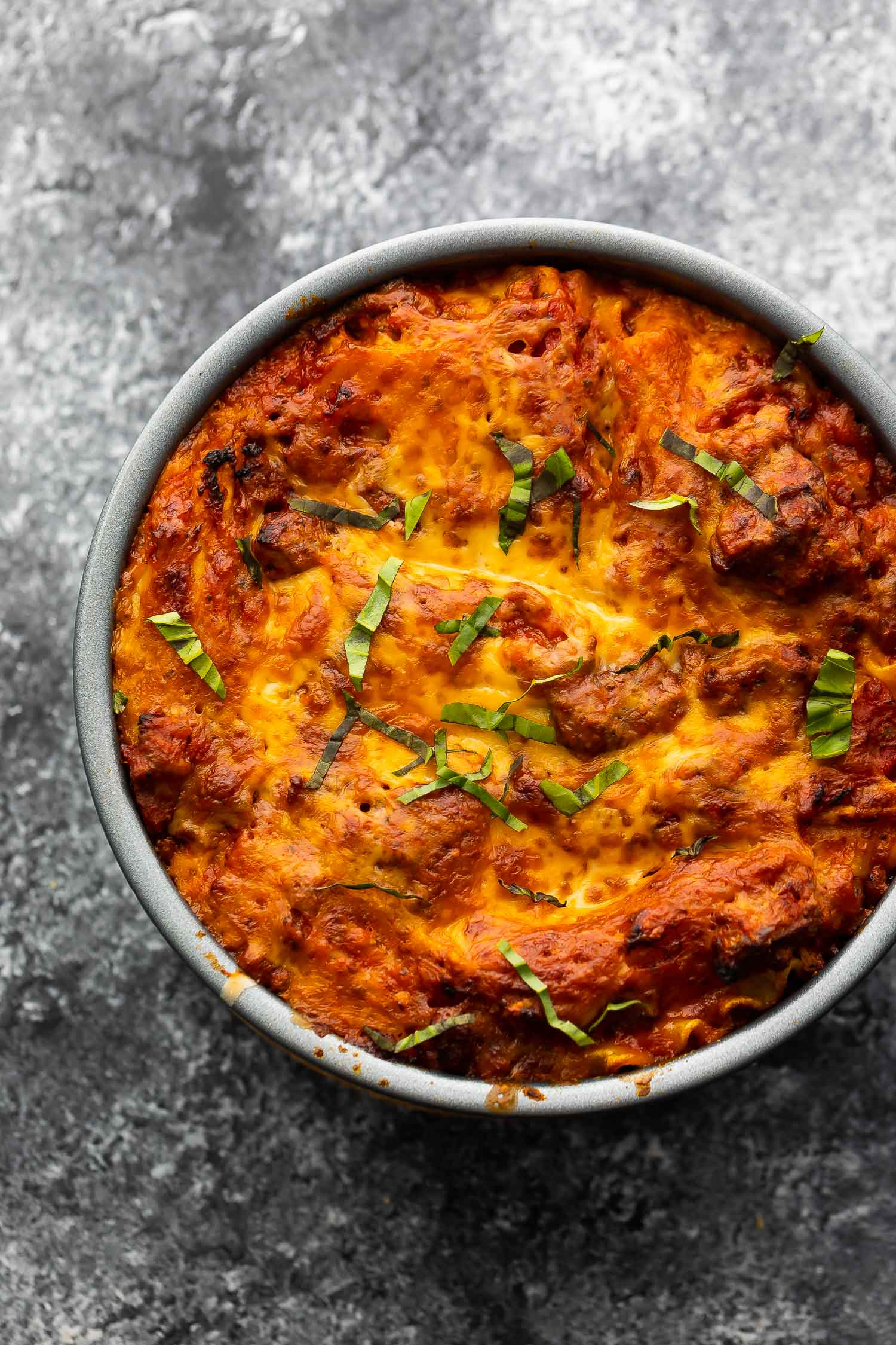 cooked lasagna in round cake pan