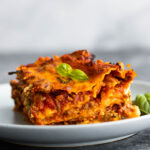 side angle view of slice of lasagna on plate topped with basil