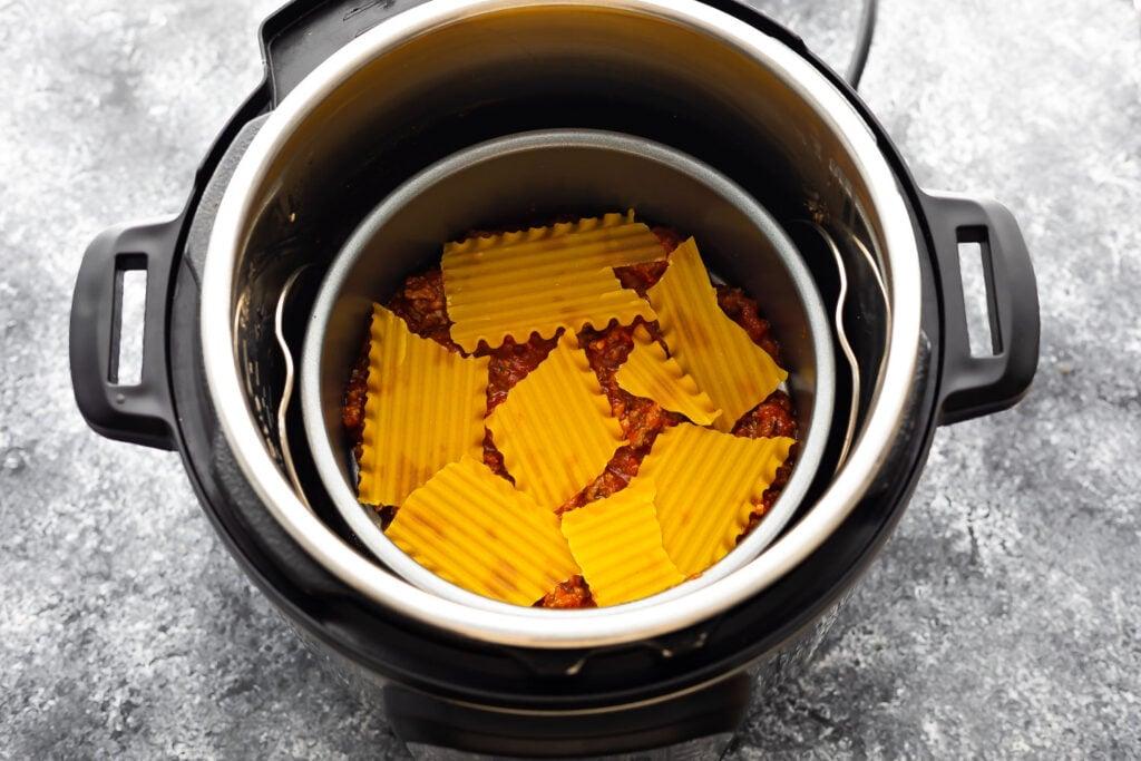 second layer of lasagna (broken noodles) in cake pan on trivet in instant pot