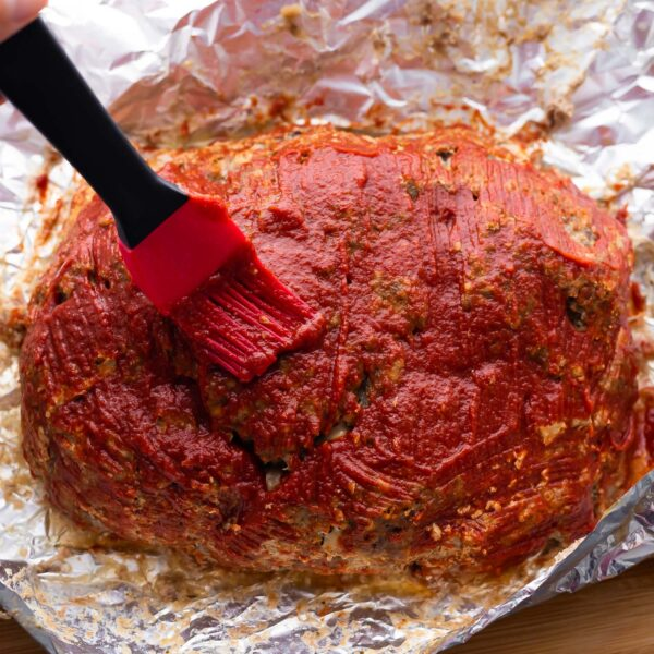 glaze being brushed onto meatloaf