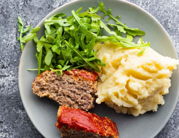 plate with two slices of meatloaf, arugula, and mashed potatoes