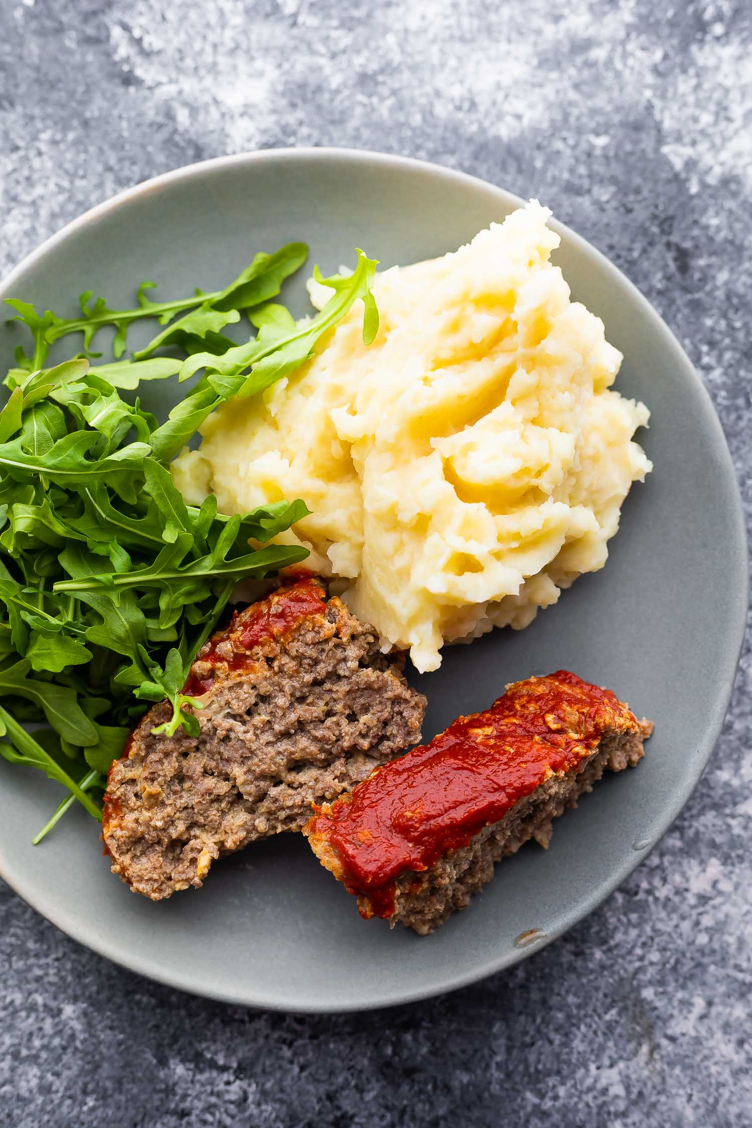 plate with two slices of meatloaf, arugula, and mashed potatoes- close up shot
