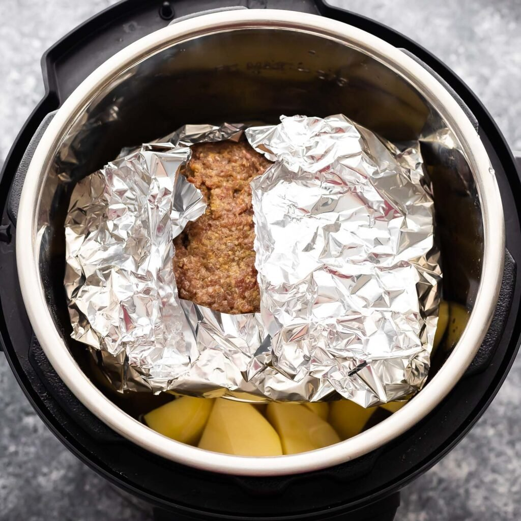 uncooked meatloaf wrapped in foil on a trivet placed over potatoes in the instant pot