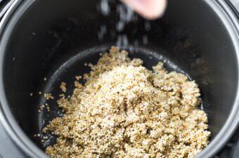 sprinkling salt into quinoa in rice cooker