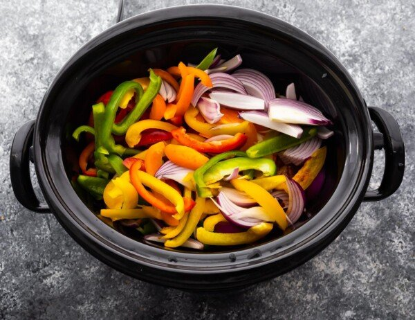 overhead view of slow cooker, bell peppers and onions added