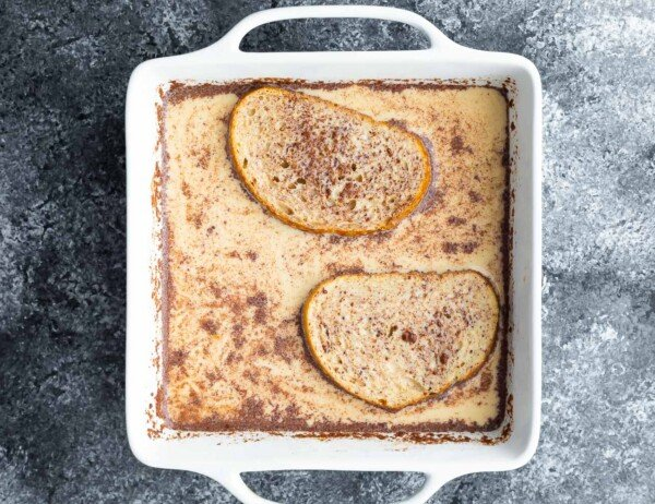 bread in french toast egg mixture in white baking dish