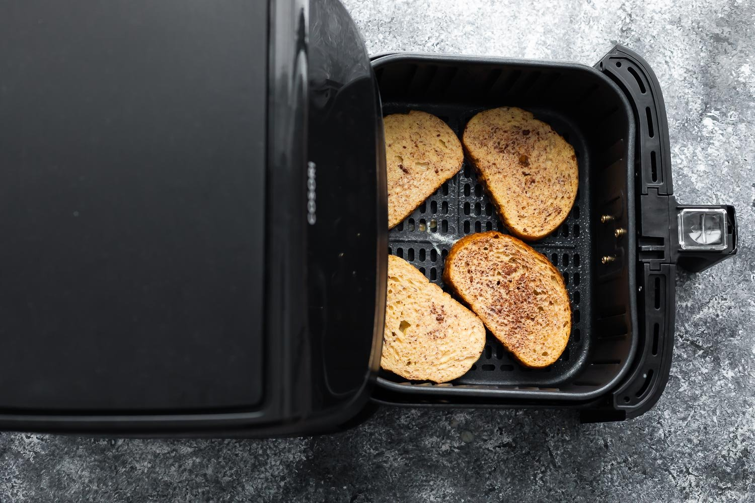 overhead view of uncooked french toast in air fryer basket before cooking through