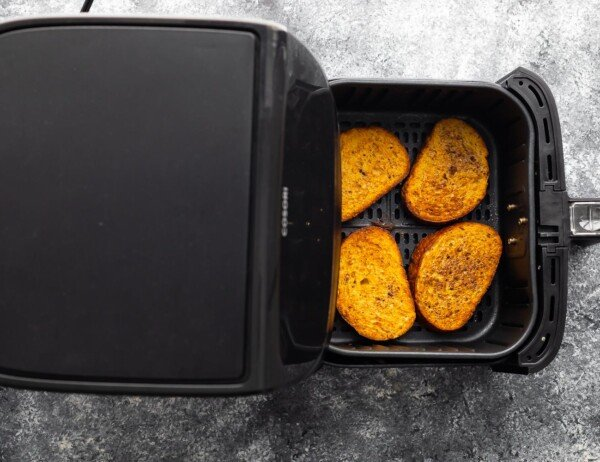 overhead view of uncooked french toast in air fryer basket after cooking through