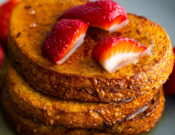 close up view of stack of air fryer french toast with strawberries and syrup