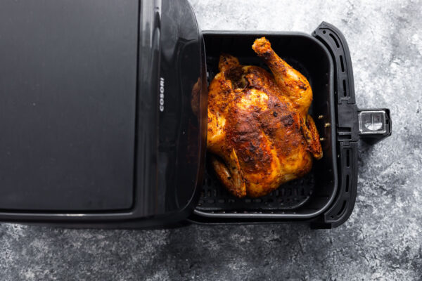 whole chicken breast side up in air fryer basket after cooking through