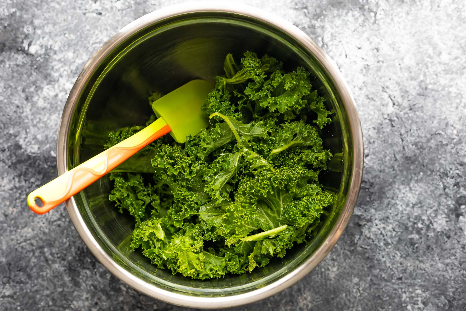 kale tossed in oil in a bowl with spatula