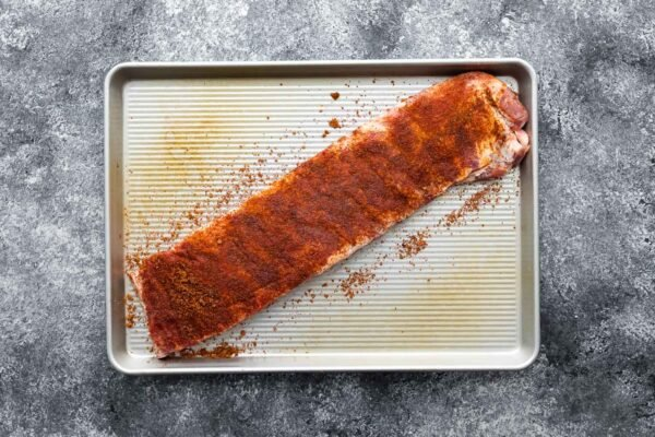 rack of ribs coated in dry rub on baking sheet