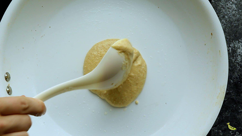 spooning pancake batter into the pan