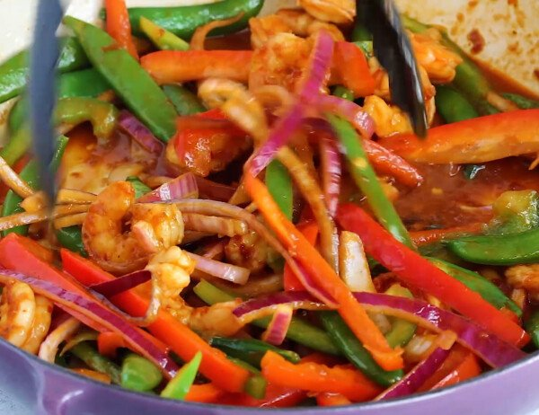 tossing shrimp and vegetables in sweet chili stir fry sauce